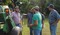 Four male students listening to a male instructor standing in front of green and yellow John Deer tractor.