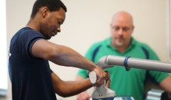 Engineering student operates robotic arm while instructor looks on.